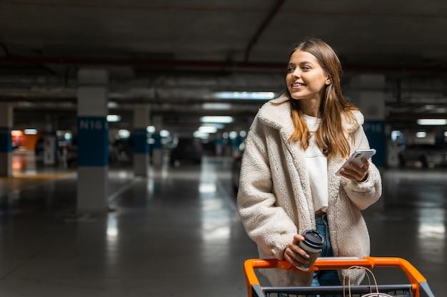 지하 주차장에서 스마트 폰 및 쇼핑 트롤리를 가진 여자