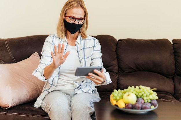 Woman with smartphone and cotton mask at home during quarantine