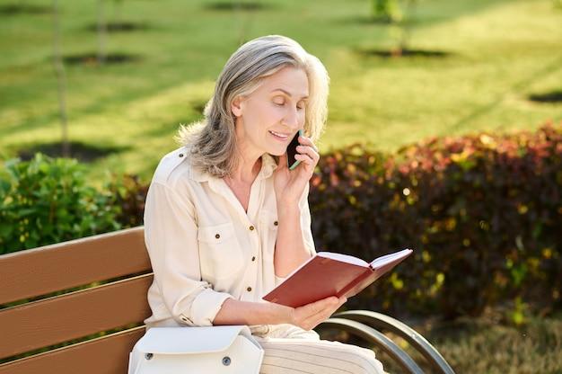 ノートブックを読んで耳の近くにスマートフォンを持つ女性