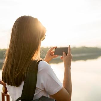 Женщина со смартфоном, фотографируя вид во время путешествия