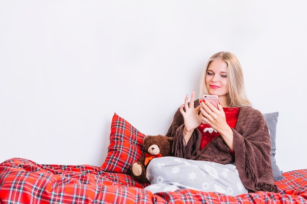 Woman with smartphone sitting on bed