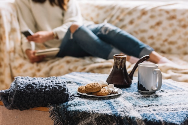 Woman with smartphone on sofa near table with drink and cookies