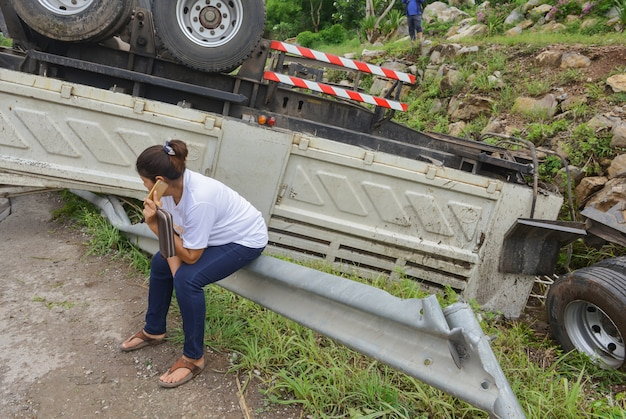 Woman with smartphone tell to her relatives after truck accident.