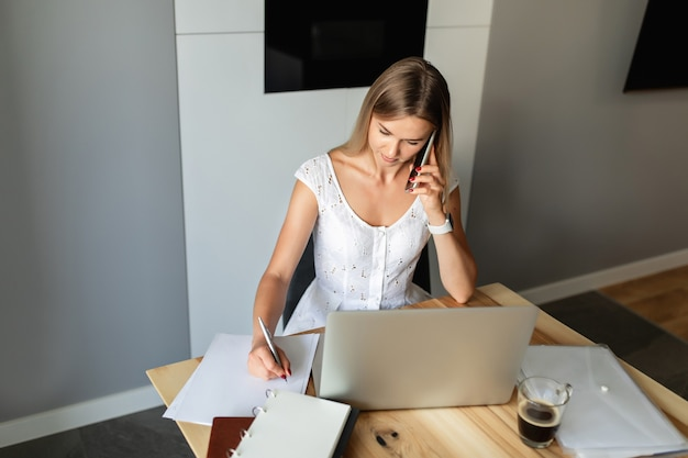 Woman with smartphone working on laptop at home office