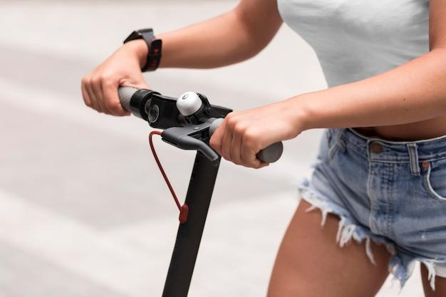 電動スクーターに乗ってスマートウォッチを持つ女性