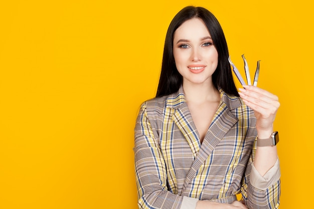 A woman with a smile holds tweezers in her hands, on a yellow wall, to the right of the text space. the concept of eyelash extensions, profession lash maker.