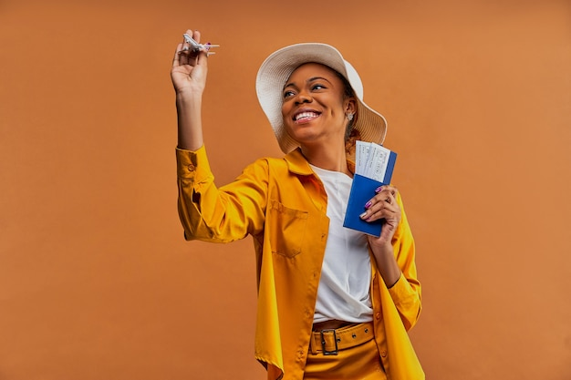 Woman with a smile in a white hat in yellow shirt with a toy airplane with a passport with tickets in hands. travel concept