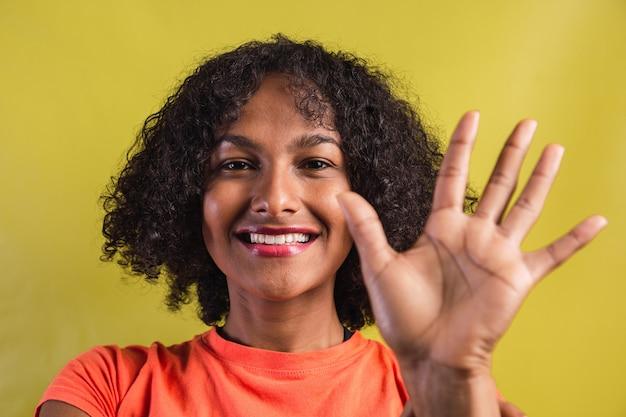 手でハイタッチをする笑顔のアフロスタイルの女性。