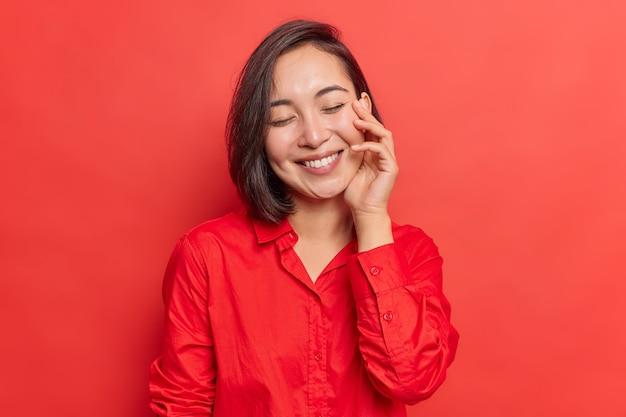滑らかで健康的な肌の笑顔を持つ女性は幸せに目を閉じたままで良い気分で赤で隔離のカジュアルなシャツを着ています