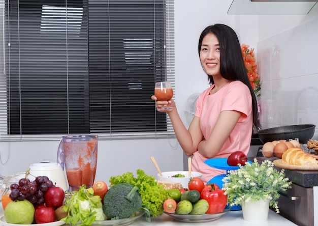 Woman with smoothies in glass at kitchen room