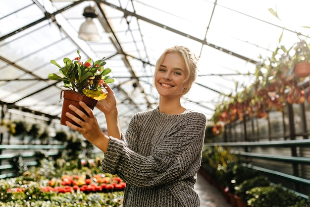 Woman with snow-white smile, holding plant with red flowers. portrait of woman in gray sweater in greenhouse.