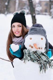 Woman with a snowman and a snowball in the shape of a heart