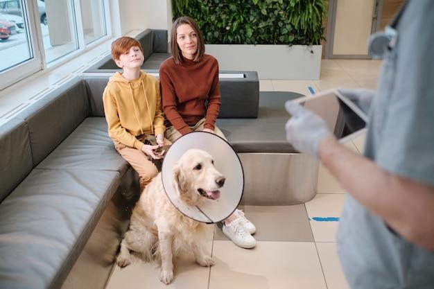 息子と犬を連れた女性がクリニックの獣医と相談する