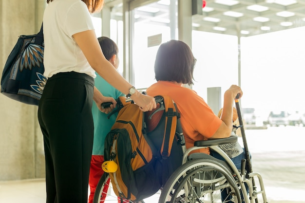 Woman with son and mother in wheelchair waiting for boarding at international airport.