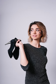 Woman with spangles on face holding shoes