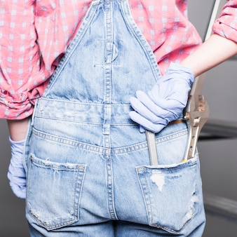 Woman with spanner in back pocket of overall