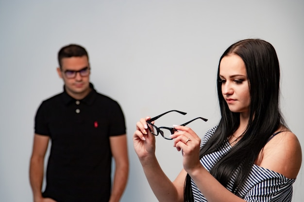 Женщина с очками в руках. человек в очках на размытом фоне. белый фон.