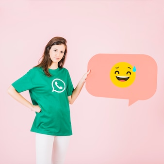 Woman with speech bubble showing smiling face and cold sweat emoji