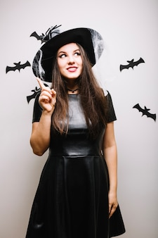 Woman with spider hat pointing up