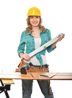 Женщина с уровнем духа и шлемом на работе