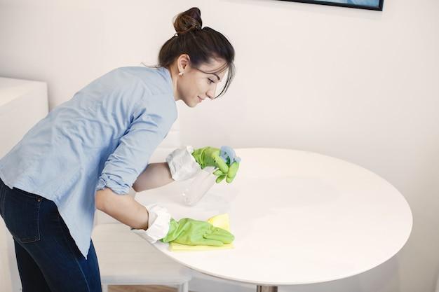 Женщина с губкой и резиновыми перчатками убирает дом