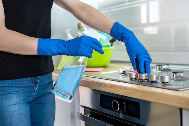 オーブンレンジトップを拭くために使用されるスポンジとゴム製の保護手袋を持つ女性