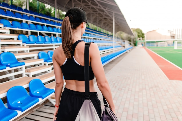 Woman with sport bag before training on the stadium in the morning