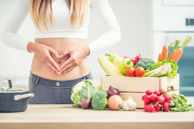 Женщина со спортивной фигурой на животе показывает форму сердца на домашней кухне с деревянной коробкой, полной органических овощей.