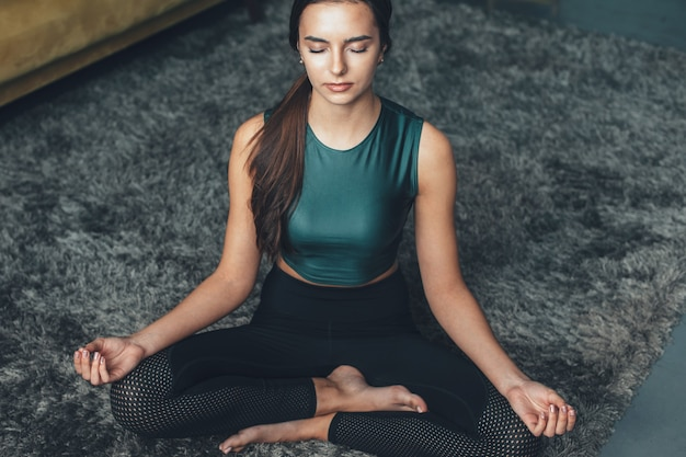 Woman with sporty clothes is meditating on the floor with closed eyes