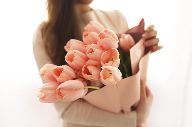 春の花の花束を持つ女性。花の匂いがする幸せな驚きのモデルの女性。母の日。女性の日。春の花の構成。