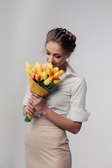 Woman with spring flower bouquet. happy surprised model woman smelling flowers.