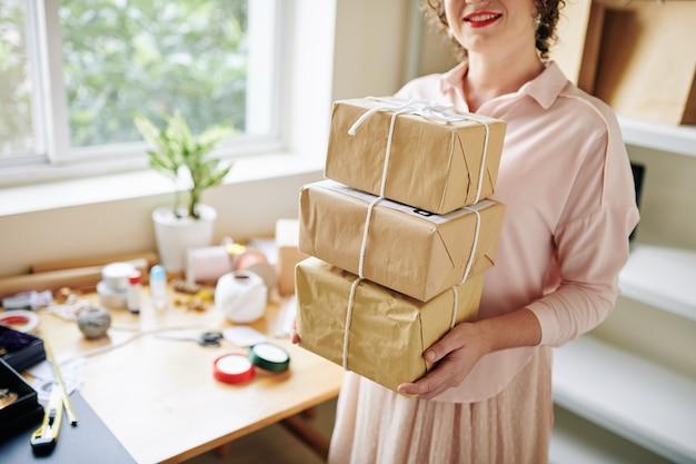 小包のスタックを持つ女性