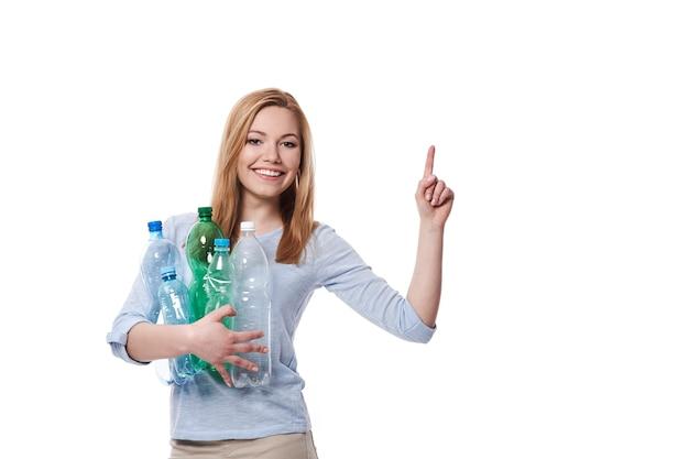 복사 공간에서 가리키는 플라스틱 병의 스택을 가진 여자
