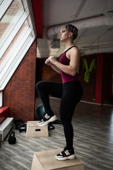 Woman with step platform doing cross fit exercise. studio shot