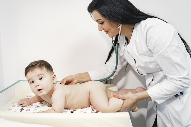 聴診器を持つ女性。おむつの赤ちゃん。おなかの上に横たわっている赤ちゃん。