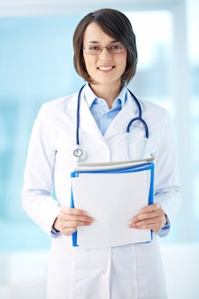 Woman with stethoscope holding a clipboard