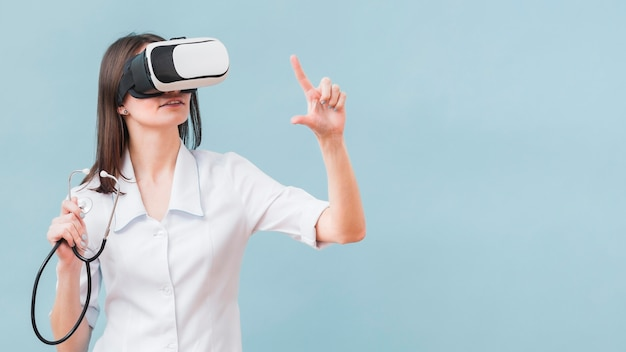 Woman with stethoscope using virtual reality headset
