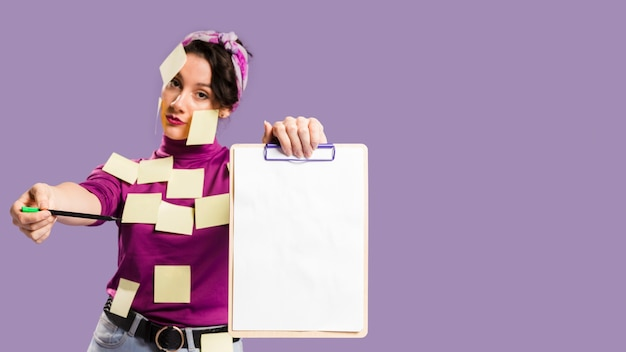 Woman with sticky notes on her holding a clipboard with copy space