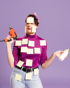Woman with sticky notes on her holding drill and baby bottle front view