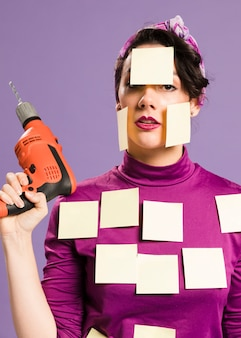 Woman with sticky notes on her holding drill