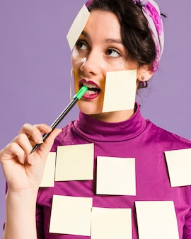Woman with sticky notes on her holding a pen