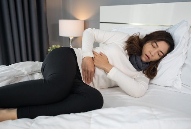 Woman with stomach ache in bed