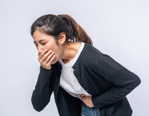 A woman with a stomachache puts her hands on her stomach and covers her mouth.