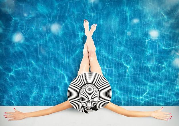 수영장에서 밀 짚 모자를 가진 여자