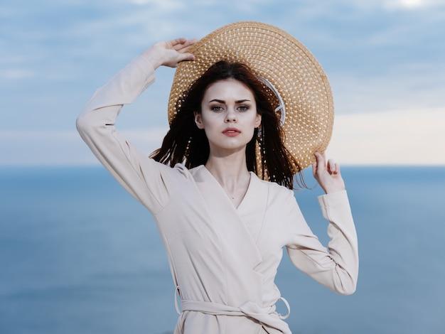海の近くで麦わら帽子をかぶった女性