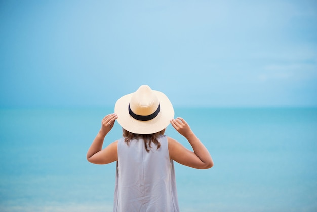 Woman with straw hat relaxing on the beach.