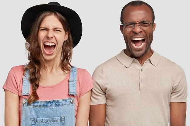 スタイリッシュな黒い帽子とオーバーオールと丸い眼鏡をかけている男と女