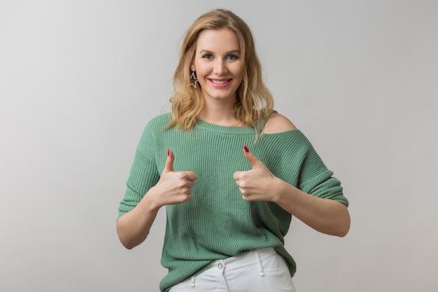 Женщина со стильным макияжем и зеленым свитером позирует на розовом