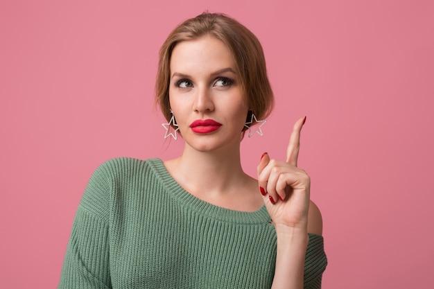 Женщина со стильным макияжем, красными губами, зеленым свитером позирует на розовом
