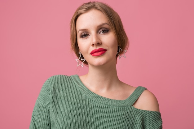 Woman with stylish make-up, red lips, green sweater posing on pink